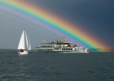 Bild von einem fahrendem Boot auf dem Chiemsee mit einem Regenbogen