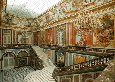 Bild von einem großen Raum mit Treppen und Gemälden in dem Schloss