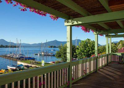 Foto von einer Terrasse und im Hintergrund ein Ufer mit Ruderbooten beim Chiemsee
