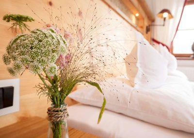 Vase mit Blumen auf dem Nachttisch
