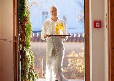 Eine Bedienung geht mit Getränken durch die Tür